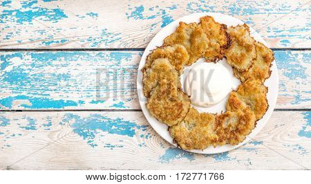 Potato pancakes with sour cream on the plate. Top view.
