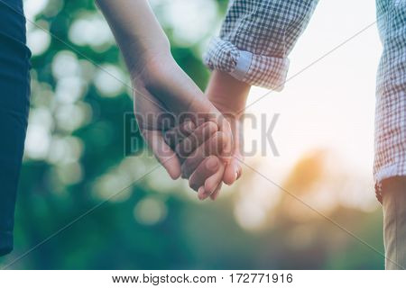 Close up of a couple holding hands. Hand-in-hand. Couple love in forest.