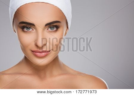 Smiling girl with brown hair fixed behind, clean fresh skin, big eyes and naked shoulders wearing white bandage, posing at gray studio background, a model with light nude make-up, copy space.