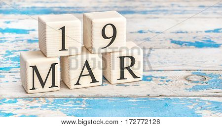 March 19th. Wooden cubes with date of 19 March on old blue wooden background.