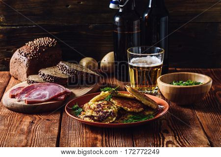 Glass of Beer with Potato Pancakes Smoked Meat and Rye Bread.