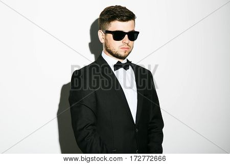 Attractive man with black hair and beard wearing white shirt with bowtie, smoking and sunglasses at white studio background, portrait, copy space, posing.
