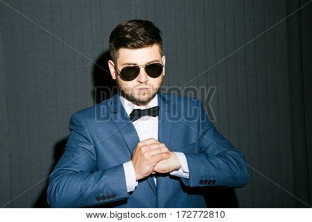 Young man in sunglasses wearing suit with bow. Serious man, fists clenched, looking down. Waist up, studio, indoors