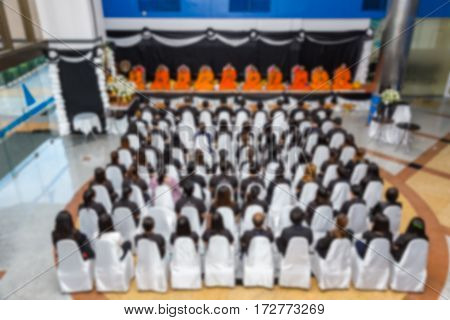 Blurr background photo of people and monks doing praying activities in Thailand