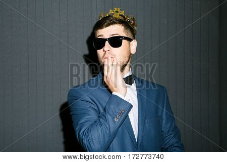 Man in sunglasses wearing suit with bow and crown on head. Looking aside, closing mouth with hand. Embarrassed, said too much. Waist up, studio, indoors