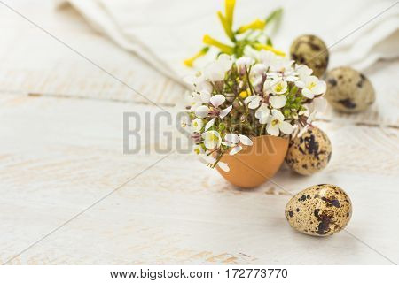 Small spring yellow white flowers in eggshell quail eggs white napkin on wood background Easter decoration soft colors close up