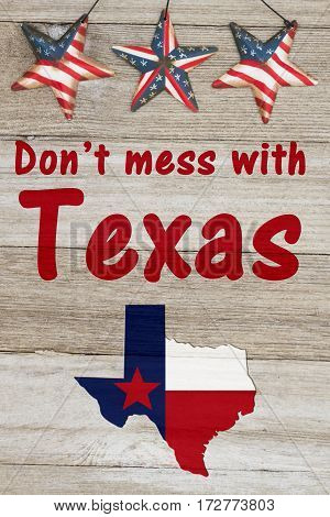 A rustic patriotic Texas message Map of Texas with the Texas Flag colors on weathered wood background with text Don't mess with Texas