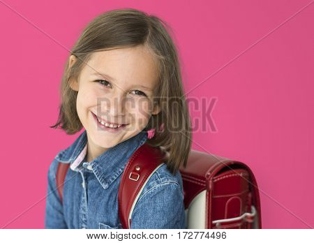 Young girl with a backpack cheerful studio portrait