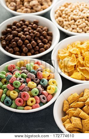 Variety of cold cereals in white bowls, quick breakfast for kids