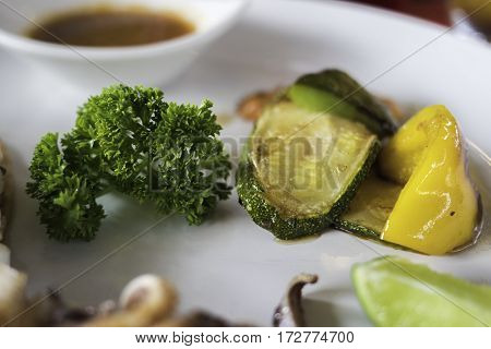 Vegetables on a white plate on a wooden table.
