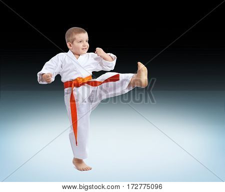 Boy in karategi hits a kick on a gradient background