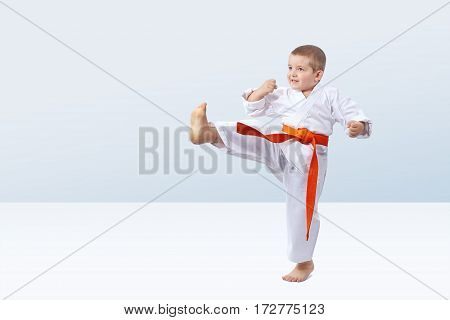Kick leg is beating small athlete on the light background