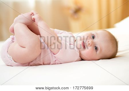 Funny chubby baby infant girl playing with feet