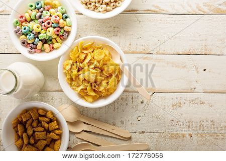 Variety of cold cereals in white bowls on white wooden table, quick breakfast for kids overhead shot with copyspace