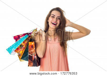 Merry girl holds in his hand a lot of bright packages with purchases and put her hand on my head isolated on white