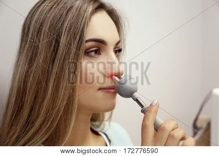 Young woman undergoing light treatment in modern clinic
