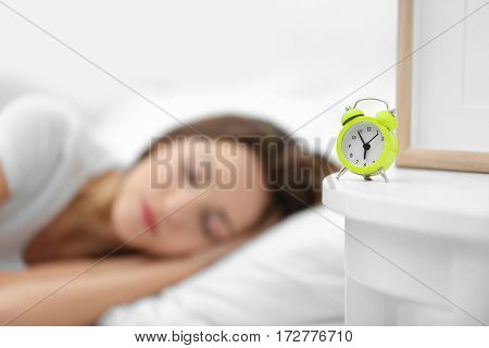Clock on bedside table in room with sleeping young woman