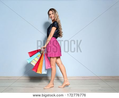 Woman with shopping bags on light wall background