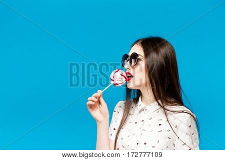 Young Beautiful Woman Holding Lollipop Isolated On Blue Background. Happy Girl Wearing Sunglasses Ea