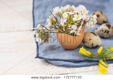 Easter interior decoration bouquet of white yellow flowers in eggshell quail eggs blue napkin on wood table close up