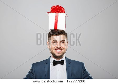 Man in suit with bow. Man with birthday present on head. Looking at camera and smiling surprisingly. Head and shoulders, studio, indoors