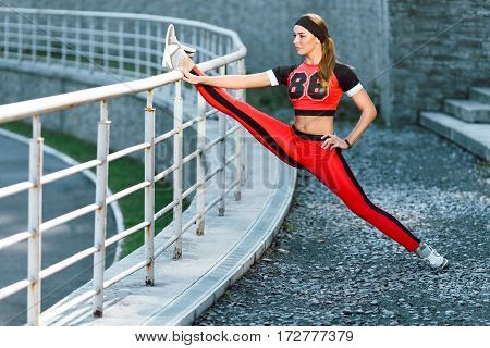 Sport, exercises outdoors. Girl in orange and black training suit doing stretching on stadium. One leg on crossbar, doing split, stretching leg. Full body, profile