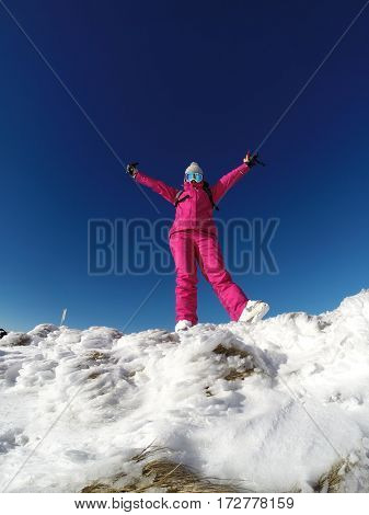 Happy young female skier on the top of snowy mountain