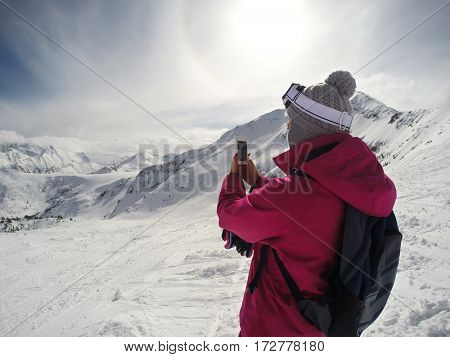 Girl photographing mountain peaks on skiing terrain