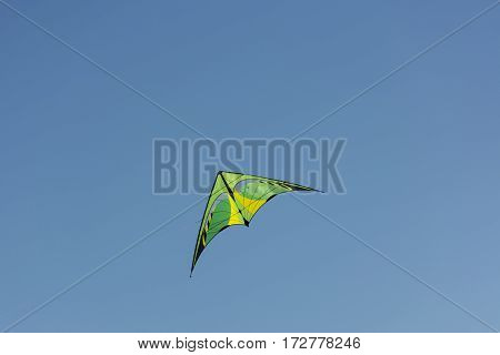 kite yellow and green colors flying in the blue sky Sunny day