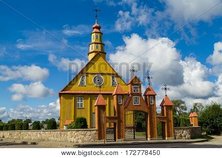 The old wooden church against blue cloudy sky in Varniai (Varniai , is a city in the Telšiai County, western Lithuania)