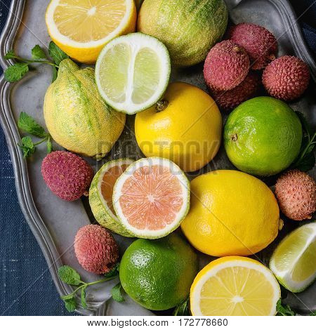 Variety of whole and sliced citrus fruits pink tiger lemon, lemon, lime, mint and exotic lichee on vintage metal plate with textile over dark blue canvas textured background. Top view. Healthy eating