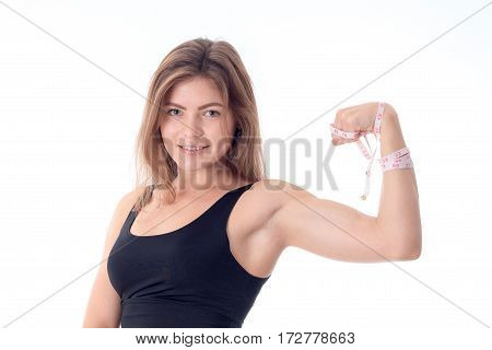 close-up of a beautiful slender athletic girl who is smiling and showing his biceps hands