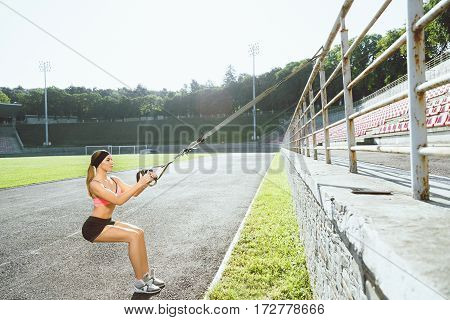 Sport, exercises with training loop outdoors. Profile of girl in rose top and black shorts doing exercises with training loop on stadium. Sporty woman in good shape squatting with training loop, full body