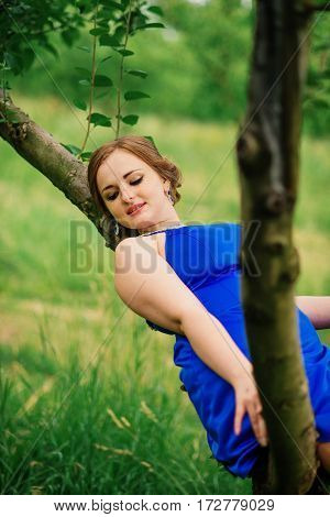 Young Overweight Girl At Blue Dress Posed Background Spring Garden Sitting On Tree.