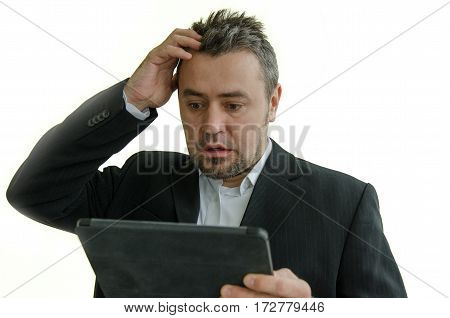 surprised and frustated businessman looking at tablet screen