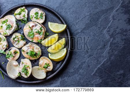 Fresh raw clams with lemon, herbs and white wine on blackiron plate on stone slate background. Top view. Free space for text