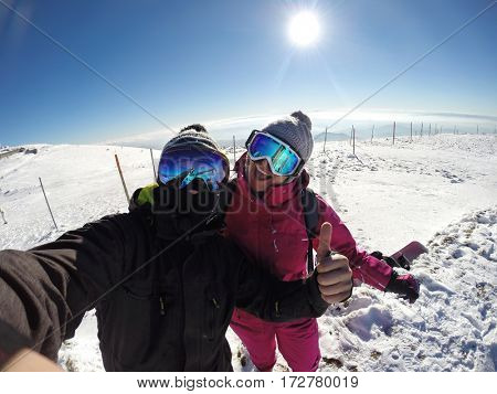 Happy couple enjoy together on skiing in snowy mountain
