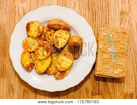 Delicious crispbread tied with organic blue thread on wooden oak table next to baked patatoes
