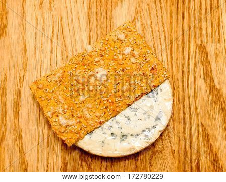 Fourme d'Ambert French chees with slice of delicious crispbread on wooden oak table