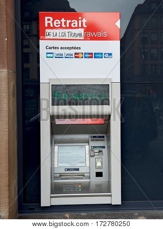 PARIS FRANCE - MAY 14 2016: HSBC ATM automatic teller machine with the protester sticker inscription Retrait de la loi travail - translating as Withdrawal of labor law