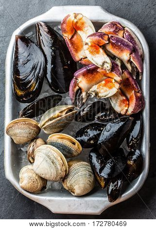 Uncooked raw fresh seafood - mussels, clams, vongole and crabs on ice on blac stone slate background
