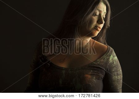 Portrait of indian woman covered in colored dust isolated in black background