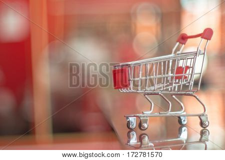 Mini red empty shopping cart with blurry background