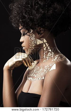 Beautiful Afro-American girl with curly hair in black dress. Make-up, hairdo, golden hand. Covered with golden patterns. Profile, hand under chin. Waist up, indoors, studio