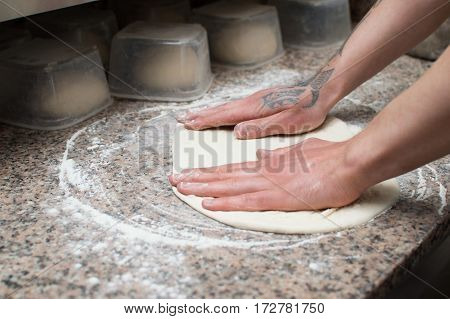 Close-up of male hands baker kneads raw pizza dough. Fast food. Pizza delivery. Baking.