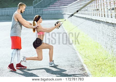 Sport, exercises with training loop outdoors. Girl in rose top and black shorts doing exercises with training loop on stadium. Coach making corrections, helping with exercises. Profile, fullbody, closeup
