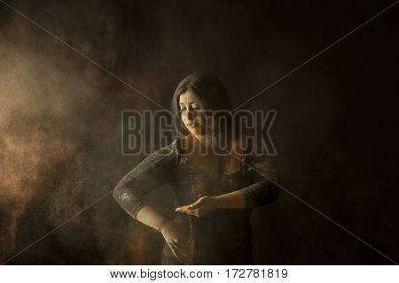 Indian woman throwing colored dust isolated on black background