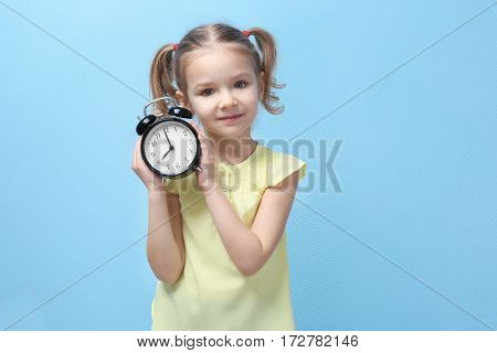 Cute little girl with alarm clock on color background