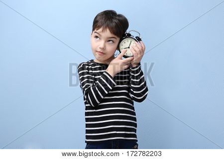 Cute little boy with alarm clock on color background