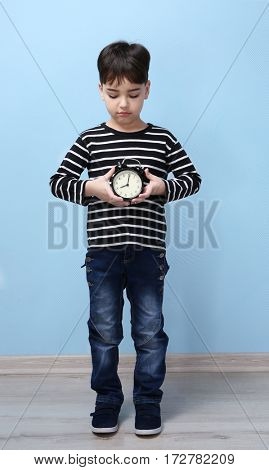 Cute little boy with alarm clock at home